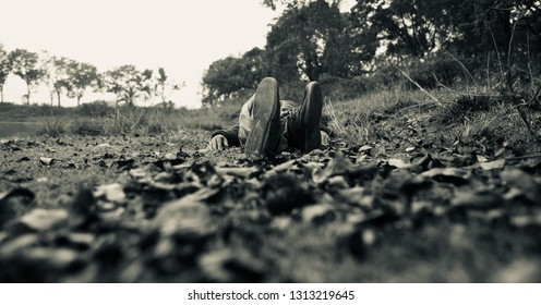 Young man wearing shoes lying on a ground unique photo