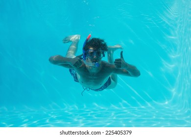 Young man wearing snorkel underwater while gesturing thumbs up