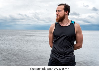Young man wearing sports clothes in the coast stretching after working out.