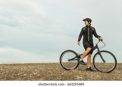Young man wearing sportswear and sitting on mountain bike among plain and looking away.