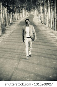 Young man wearing stylish dress walking on the road unique photo