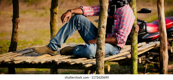 Young man wearing stylish shirt and jeans wear sitting in a place photo