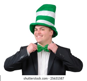 Young man wearing suit with green novelty hat, straightening green bow tie for St. Patrick's Day. Isolated