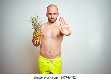 Young man wearing summer hat and swimwear holding pineapple over isoalted background with open hand doing stop sign with serious and confident expression, defense gesture
