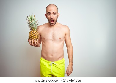 Young man wearing summer hat and swimwear holding pineapple over isoalted background scared in shock with a surprise face, afraid and excited with fear expression
