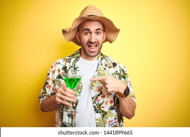 Young man wearing summer hawaiian flowers shirt and drinking a cocktail over yellow background very happy pointing with hand and finger