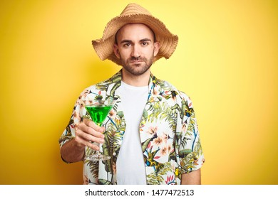 Young man wearing summer hawaiian flowers shirt and drinking a cocktail over yellow background with a confident expression on smart face thinking serious
