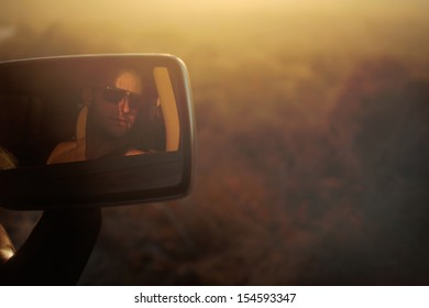 Young man wearing sun glasses during a Roadtrip in the desert on a hot summer day.
