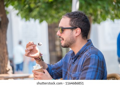 Young man wearing sunglasses, enjoying a tasty ice cream sitting on a summer terrace