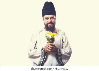 young man wearing traditional romanian costume on white background holding flowers