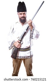 young man wearing traditional romanian costume holding an antique rifle