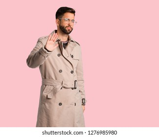 Young man wearing trench coat putting hand in front