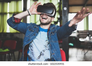 Young man wearing virtual reality glasses in modern interior design coworking studio. Smartphone using with VR goggles headset.