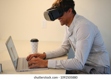 Young man wearing virtual reality glasses, with grey computer, coffee. Caucasian business looking, grey shirt.
