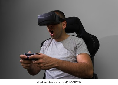 Young man  wearing virtual reality glasses and playing a videogame using a remote controler.