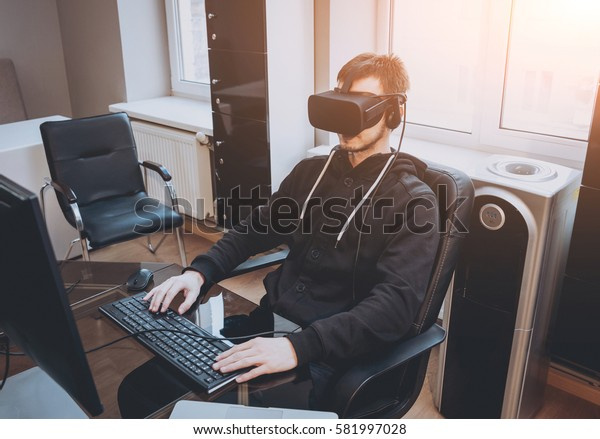 The young man wearing virtual reality goggles at the office