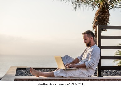 Young man wearing white cloths focused working with laptop on his laps. Warm light of sunset illuminating his face and surrounding palms trees