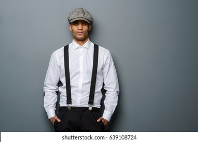 Young man wearing white shirt, suspenders and flat cap, close-up. Grey background. Hipster style.