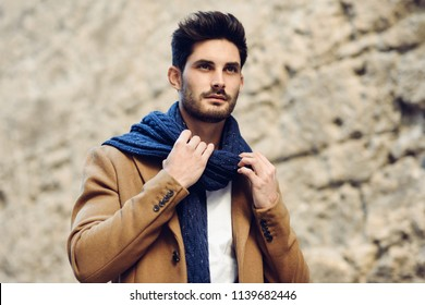 Young man wearing winter clothes in the street. Young bearded guy with modern hairstyle with coat, scarf, blue jeans and t-shirt.