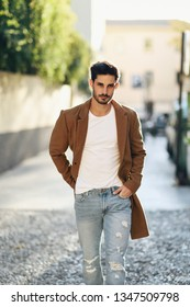 Young man wearing winter clothes in the street. Young bearded guy with modern hairstyle with coat, blue jeans and white t-shirt.
