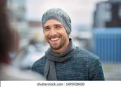 Young man wearing winter hat laughing while talking to woman. Handsome guy on a sidewalk wearing jumper and scarf. Portrait of cheerful man in winter clothes enjoying outdoor with girlfriend.