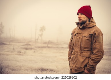 Young Man wearing winter hat clothing outdoor with foggy nature on background Travel Lifestyle and melancholy emotions concept film effects colors