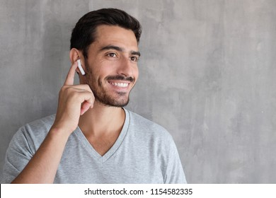Young man wearing wireless earbuds and t shirt, listening to his favorite musical album online, touching one earphone to control application