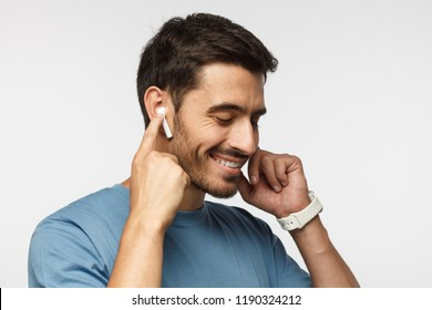 Young man wearing wireless earbuds and blue t shirt, listening to his favorite musical album online, touching one earphone to control application