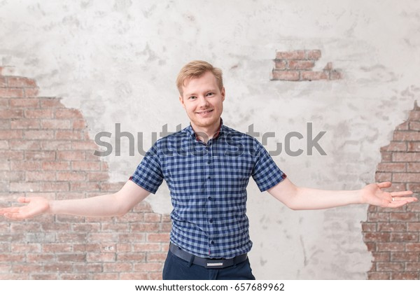Young man welcoming everyone with his open arms and a big smile. Emotions, facial expressions, feelings, body language, signs concept on white brick wall