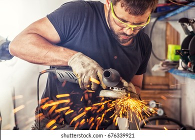 A young man welder in a black T-shirt, goggles and construction gloves processes metal an angle grinder   in the garage, in the background a lot of tools, sparks fly to the side