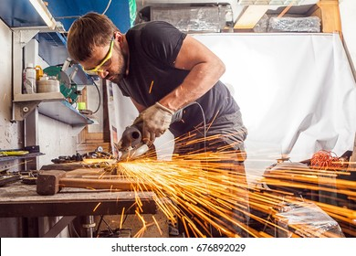A young man welder in a black T-shirt, goggles and construction gloves grinder metal an angle grinder   in the   workshop, sparks fly to the side