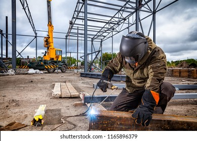 A young  man welder in brown uniform, welding mask and welders leathers, weld  metal  with a arc welding machine at the construction site, blue sparks fly to the sides