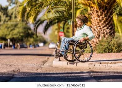Young man in wheelchair approaches high city curb
