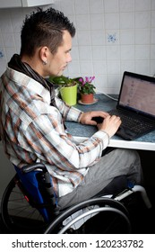 young man in wheelchair in Barrier-free apartment is using his laptop, disabled young man is surfing in internet