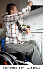 young man in wheelchair in Barrier-free apartment, disabled young man in the kitchen