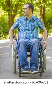 young man in a wheelchair enjoying fresh air in city park