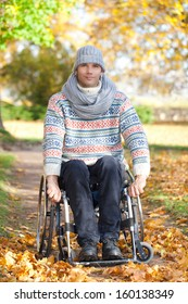 young man in wheelchair enjoying his life on sunny autumn day in park, feeling of freedom