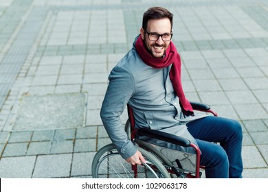 Young man in the wheelchair going outside and smiling