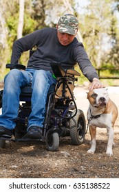 Young man in a wheelchair with his faithful dog walk in the park.