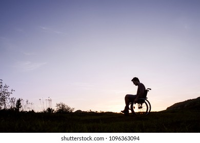 A young man in wheelchair in nature in the evening.