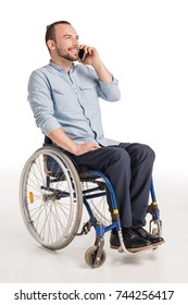 Young man in wheelchair talking on smartphone and laughing, isolated on white