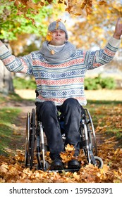 young man in wheelchair with wide opened arms enjoying his life on sunny autumn day in park, feeling of freedom