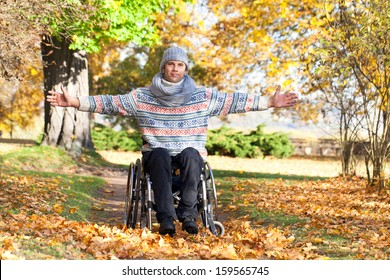young man in wheelchair with wide opened arms enjoying his life in autumn park on sunny day