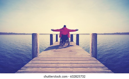 young man in wheelchair with wide opened arms enjoying his life at a lake