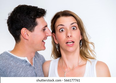 young man whisper in the ear of his girlfriend