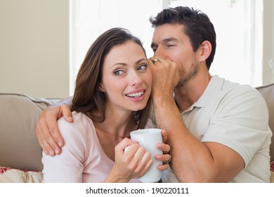 Young man whispering secret into a happy young womans ear in the living room at home