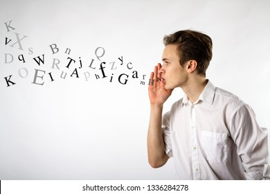 Young man is whispering at something. Whispering and letters concept.