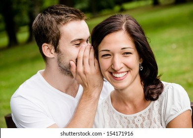 Young man whispering to woman (girlfriend) - outdoor lifestyle photo