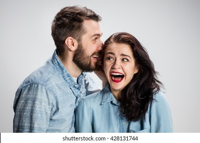 Young man whispering to woman (girlfriend) - indoor lifestyle photo on gray background