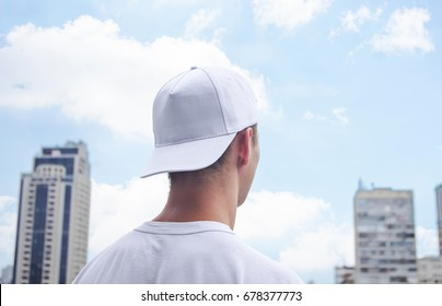 Young man in a white baseball cap and white t-shirt on background of the city and blue sky with clouds